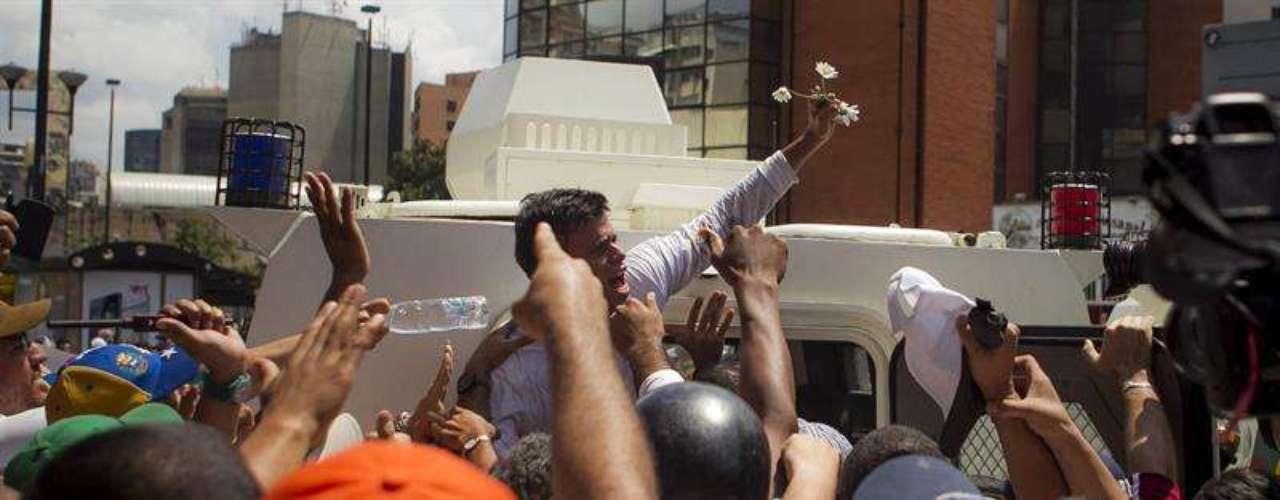 Un grupo de manifestantes impide el paso al vehículo donde se encuentra el dirigente opositor venezolano Leopoldo López antes de entregarse a miembros de la Guardia Nacional.