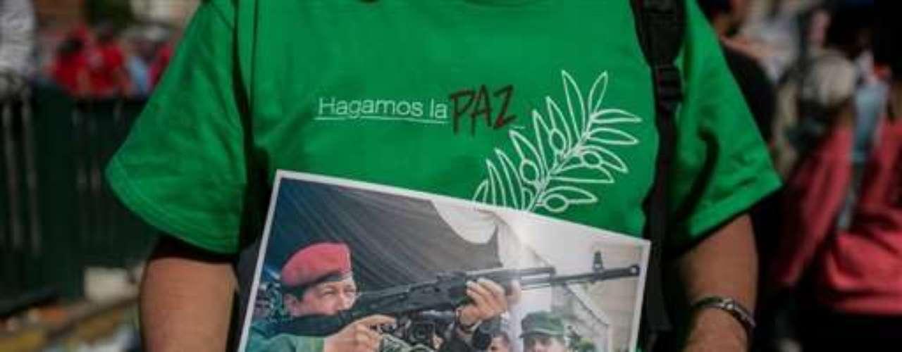 Un simpatizante del mandatario venezolano Nicolás Maduro sostiene una foto del fallecido Hugo Chávez, durante una marcha en apoyo al gobierno, en Caracas.