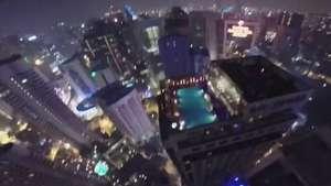 Homem salta de torre e cai em piscina de topo de prédio  Video: