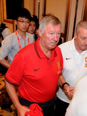 Manchester United manager Alex Ferguson (C) leaves after taking part in a press conference at a hotel in Shanghai on July 23, 2012. Man United arrived in China as part of their pre-season tour and will play the Shanghai Shenhua on July 25, the club that recently signed Chelsea Champions League hero Didier Drogba. Foto: Getty Images