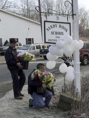Bomberos voluntarios colocan flores en un monumento improvisado en la entrada de la escuela primaria Sandy Hook el sábado 15 de diciembre de 2012 en Newtown, Connecticut. La familia de una niña boricua de 6 años que murió asesinada en la matanza en la escuela se había mudado a Estados Unidos apenas dos meses antes de la tragedia.  Foto: Mary Altaffer / AP