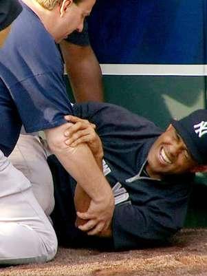 El panameño Mariano Rivera, de los Yanquis de Nueva York, al centro, hace gestos de dolor tras torcerse la rodilla izquierda mientras atrapaba bolas durante una práctica de bateo antes del partido de visita contra los Reales de Kansas City, el jueves 3 de mayo de 2012.  Foto: YES Network / AP