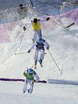El francés Jean Frederic Chapuis, en primer plano, aventaja a sus compatriotas Arnaud Bovolenta y Jonathan Midol, mientras el canadiense Brady Leman sufre una caída en la final skicross de los Juegos Olímpicos de Invierno, el jueves 20 de febrero de 2014, en Krasnaya Polyana, Rusia.  Foto: Andy Wong / AP