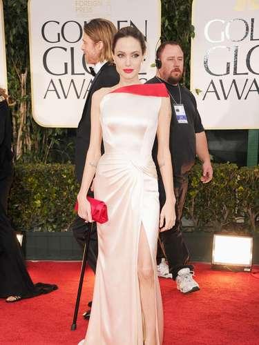 Sofisticada y dramática, así lució Angelina Jolie sobre el Red Carpet de los Golden Globes 2012 en Versace. El vestido largo en satín color crema es un diseño de corte estructural asimétrico embellecido por un pliegue en rojo en el busto, drapeado en la cadera y falda al aire con abertura frontal en la pierna. Angelina complementó su look con un mini bolso y labios rojos.