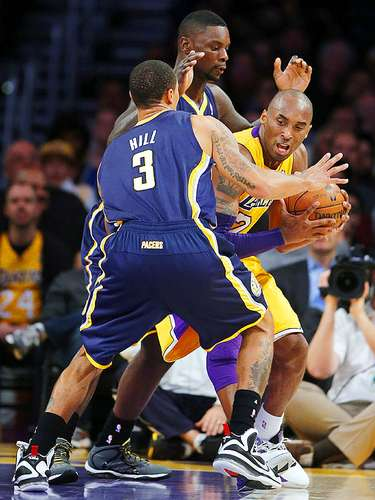 Pacers vs. Lakers: Kobe Bryant intenta superar la marca de George Hill (3) y Lance Stephenson.