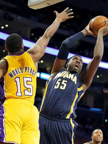 Pacers vs. Lakers: Roy Hibbert (55) intenta clavar el balón en la canasta ante la marca de Metta World Peace (15).