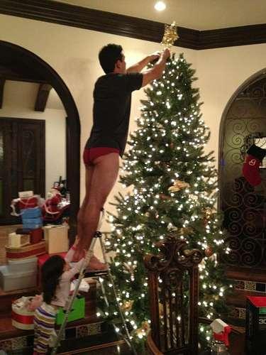 La pareja de Mario Lopez capturó con su cámara y compartió en twitter este momento 'mágico' en el que el conductor de Extra pone la estrella en la punta de su árbol navideño en calzoncillos y con sus medias