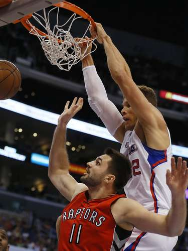 Los Angeles Clippers Blake Griffin (R) slam dunks over Toronto Raptors Linas Kleiza during their NBA basketball game in Los Angeles, California, December 9, 2012.