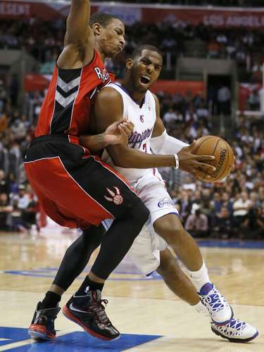 Los Angeles Clippers Chris Paul (R) drives past Toronto Raptors DeMar DeRozan during their NBA basketball game in Los Angeles, California, December 9, 2012.