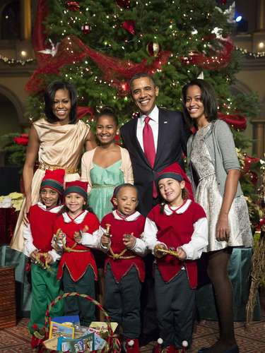 U.S. President Barack Obama, First Lady Michelle Obama, their daughters Sasha (R) and Malia, pose with children as they attend the Christmas in Washington concert at the National Building Museum in Washington December 9, 2012. Korean rapper Psy is expected to perform along with Diana Ross, Demi Lovato, Megan Hilty, Scott McCreery, and Chris Mann. REUTERS/Joshua Roberts (UNITED STATES - Tags: POLITICS ENTERTAINMENT SOCIETY)