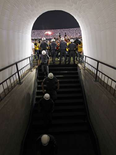 Brazilian police guard the entrance to the locker rooms as players from Argentina's Tigre refused to return to the field. The second half was delayed and eventually called off. REUTERS/Paulo Whitaker