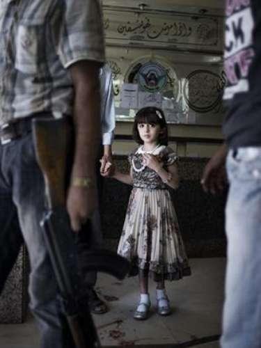 Una niña que mira atemorizada a un hombre con un rifle Kalashnikov en la sala de un hospital de Siria con el suelo manchado de sangre: es la \