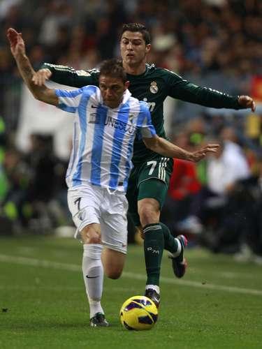 Real Madrid's Cristiano Ronaldo (back) challenges Malaga's Joaquin Sanchez.