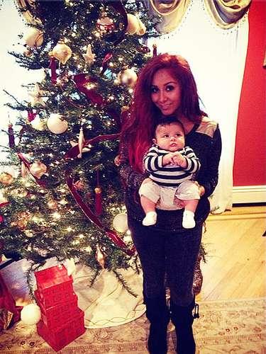 Snooki y su pequeño ángel Lorenzo posan juntos frente al arbolito navideño.