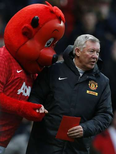 Manchester United's manager Alex Ferguson walks to his seat with a friend. REUTERS/Phil Noble
