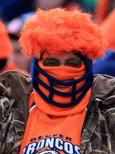 A masked Denver Broncos fan suports his team in the AFC playoff game at the Sports Authority Field in Denver.