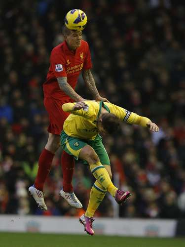 Liverpool's Daniel Agger (top) challenges Norwich City's Grant Holt. REUTERS/Phil Noble