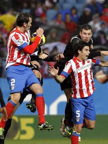 El defensa uruguayo del Atlético de Madrid Diego Godín (i) y el centrocampista portugués Tiago Méndez (d), durante el partido de la vigésima jornada de la liga disputado esta tarde en el estadio Vicente Calderón