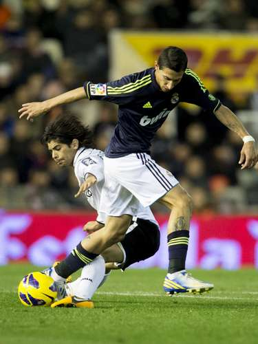 Angel di Maria tries to get past a Valencia defender. The Real Madrid winger was shown a red-card in the second half, one of two Real players who were ejected.