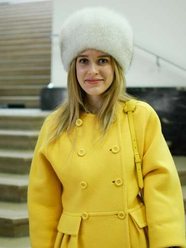 El abrigo amarillo se volvió más llamativo con accesorios blancos.