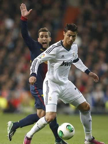 Real Madrid's Cristiano Ronaldo (R) controls the ball against Barcelona's Jordi Alba.