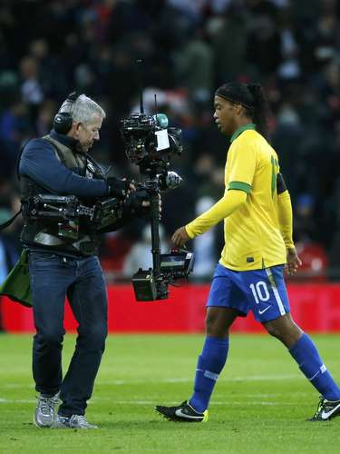 A television camera follows Brazil's Ronaldinho (R) off the pitch at halftime during the international friendly.