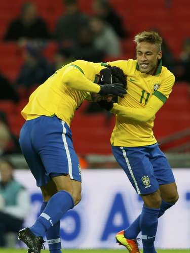 Brazil's Fred (L) celebrates with team mate Neymar after scoring the equaliser against England.