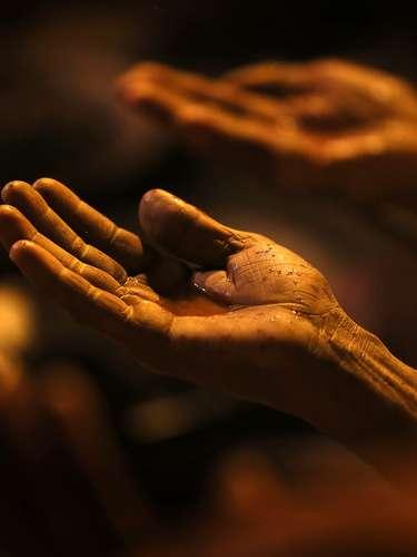 Un hombre santo hindú de la secta Juna Akhara con agua sagrada en la palma de su mano durante las celebraciones del Maha Kumbh a orillas del río Ganges