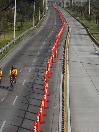 Dos ciclistas por una avenida de Bogotá que conduce al aeropuerto vacía de coches durante la celebración del día sin coches