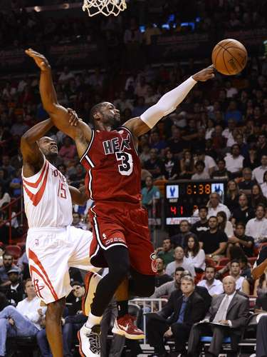 Miami Heat's Dwyane Wade (R) is fouled by Houston Rockets' Toney Douglas (L) during the first half of their NBA basketball game in Miami, Florida, February 6, 2013.