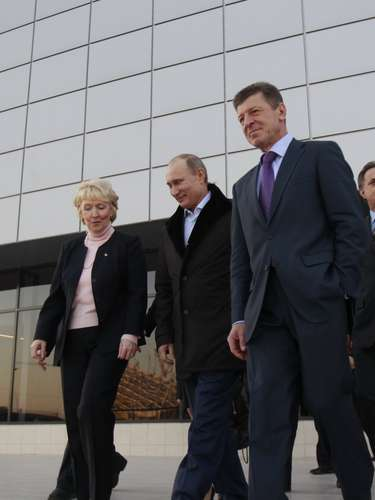 Russian President Vladimir Putin walks with Deputy Prime Minister Dmitry Kozak (R) near the Ice Cube Curling Centre to be used in the 2014 Winter Olympics.