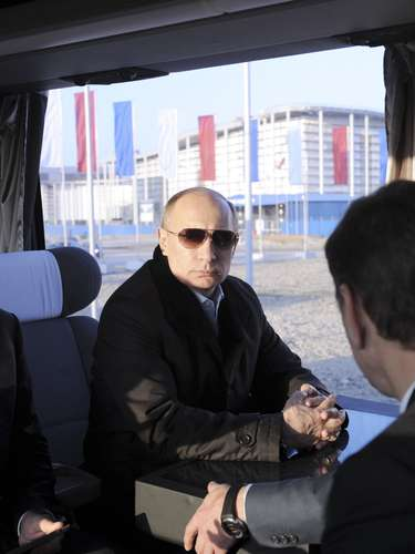 Russia's President Vladimir Putin (C) rides in a bus with the head of the Sochi 2014 organising committee Dmitry Chernyshenko (L).