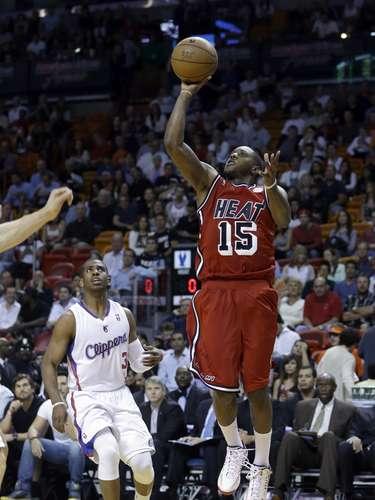 Mario Chalmers (15) de Miami Heat dispara al arco ante los defensivos de los Clippers de Los Ángeles