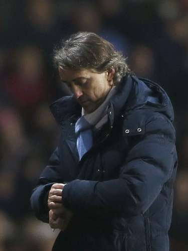 Manchester City's Manager Roberto Mancini checks his watch as his team was losing 3-1