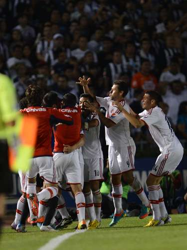 The Rebano striker is surrounded by his teammates after the goal.