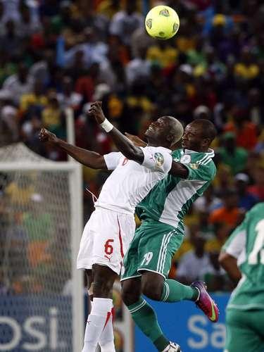 Burkina Faso's Djakaridja Kone challenges Nigeria's Sunday Mbah (R).