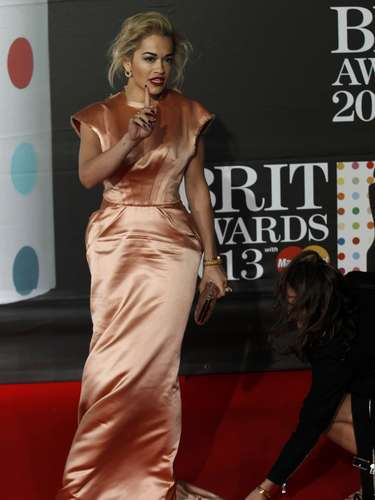British singer Rita Ora has her clothing adjusted as she arrives for the BRIT Awards, celebrating British pop music, at the O2 Arena in London February 20, 2013. REUTERS/Luke Macgregor (BRITAIN  - Tags: ENTERTAINMENT)