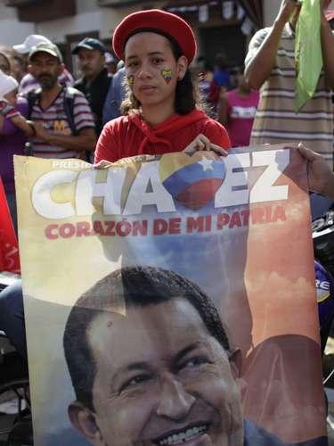 Una niña sostiene una foto de Hugo Chávez el 6 de marzo del 2013 frente al hospital de Caracas donde falleció el presidente venezolano. El gobierno decretó siete días de luto y se suspendieron las clases por una semana. (AP Photo/Ariana Cubillos)