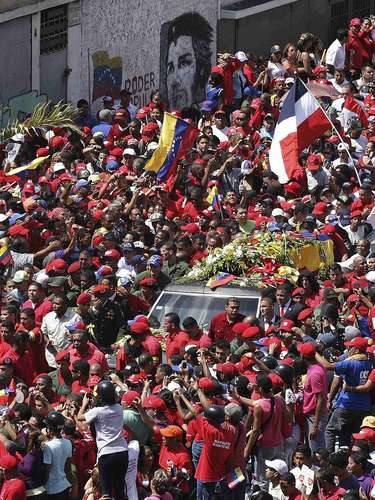 The coffin of Venezuela's late President Hugo Chavez is driven through the streets of Caracas after leaving the military hospital where he died of cancer, in Caracas, March 6, 2013. Authorities have not yet said where Chavez will be buried after his state funeral on Friday. REUTERS/Christian Veron (VENEZUELA - Tags: POLITICS OBITUARY)