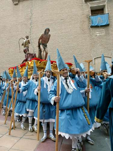 Nazarenos estantes portan el paso con el grupo escultórico de la Sagrada Flagelación en la procesión de la Cofradía del Cristo del Amparo de Murcia. Los estantes lucen el capirote de habichuela, que no acaba en punta, y con la cara descubierta.