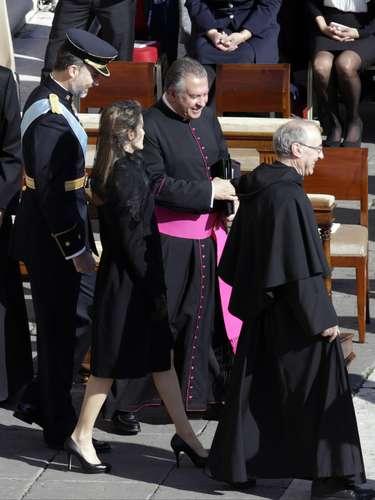 Letizia ha lucido abrigo negro. En la imagen, junto al Príncipe y un religioso.