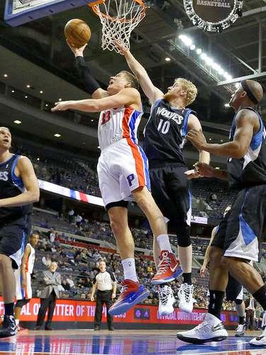 Timberwolves vs. Pistons:Jonas Jerebko (33) intenta una canasta ante la marca deChase Budinger (10).