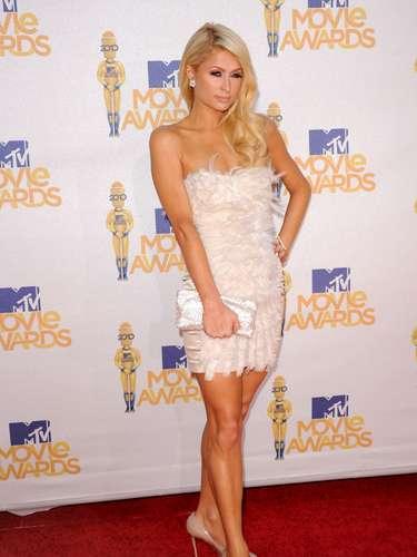 2010 - Paris Hilton. La rubia lució súper sensual en la alfombra roja, el glamur del minivestido blanco adornado de plumas, es espléndido. Los pendientes de diamantes que escogió como accesorios en flor más su bolso y los anillos, le dieron al elegancia precisa.