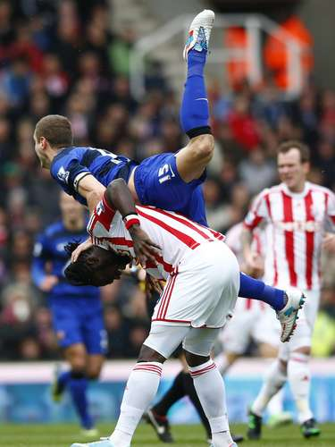 Manchester United's Nemanja Vidic (top) challenges Stoke City's Kenwyne Jones. REUTERS/Darren Staples