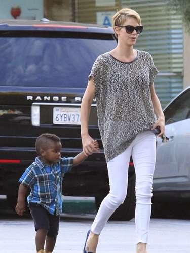 Charlize Theron lleva a su pequeño a la guardería con pantalones pitillo en color blanco, camisa con print animal y bailarinas en azul klein.