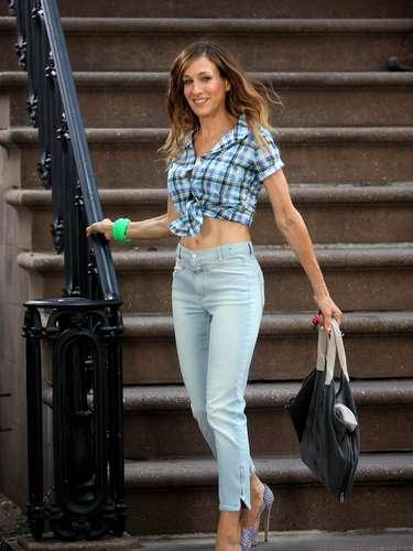 Sarah Jessica Parker se atreve a enseñar el ombligo con su camisa anudada. La actriz apuesta por una de manga corta combinada con vaqueros de tiro alto y stilettos de color morado.