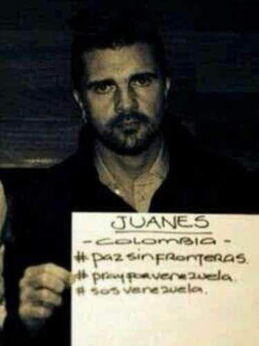Juanes sostiene un cartel que dice: \