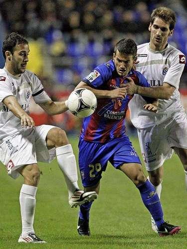 El centrocampista del Levante Rubén García (c) disputa un balón con los jugadores del Melilla, el defensa Sánchez (i) y el centrocampista Fausto Tienza (d), durante el partido de vuelta de los dieciseisavos de final de la Copa del Rey, disputado esta noche en el estadio Ciutat de Valencia.