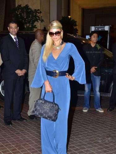 Con este vestido azul enterizo llegó al aeropuerto. Un look perfecto que supo combinar con accesorios de todo tipo: diadema en el pelo, lentes, collar, cinturón azul oscuro, bolso by Paris Hilton y zapatos en tono gris.