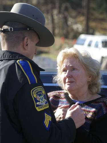 A woman speaks with a Connecticut State Trooper outside Sandy Hook Elementary School after a shooting in Newtown, Connecticut, December 14, 2012. A shooter opened fire at the elementary school in Newtown, Connecticut, on Friday, killing several people including children, the Hartford Courant newspaper reported. REUTERS/Michelle McLoughlin (UNITED STATES - Tags: CRIME LAW EDUCATION)
